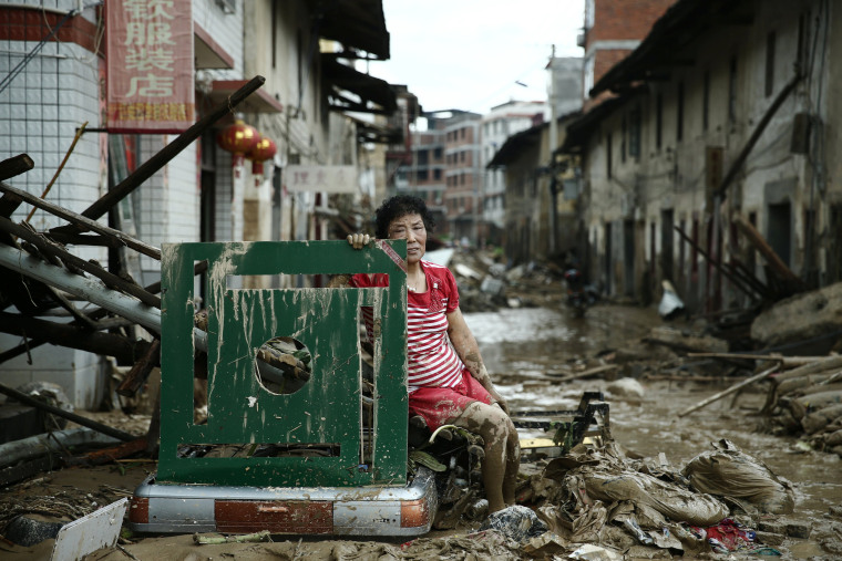 Image: A woman sits on the ruins after typhoon Nepartak swept through Minqing county