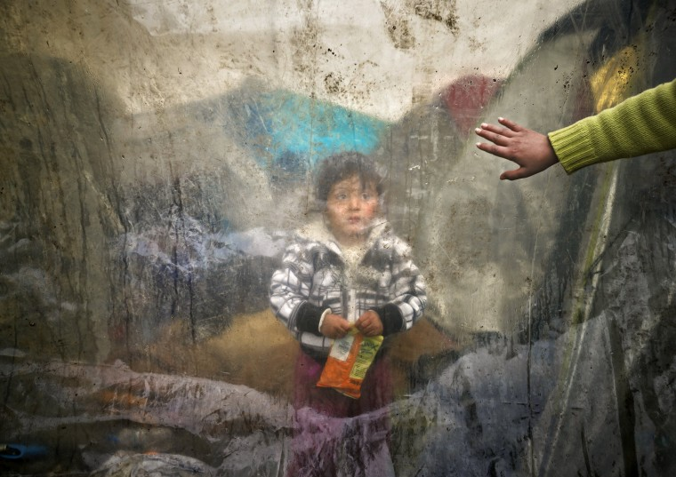 Image: A migrant baby sits behind plastic sheets covering tents