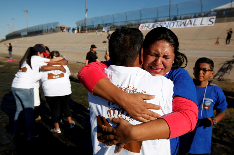 Relatives separated by deportation and immigration hug at the border during a brief reunification meeting at the banks of the Rio Bravo, a natural border between U.S. and Mexico