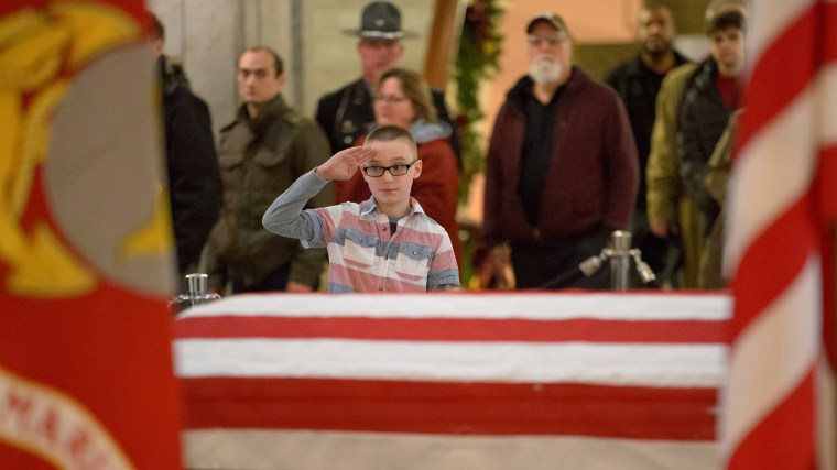 Image: A young man pays his respects to former astronaut and U.S. Senator John Glenn as he lies in repose, under a United States Marine honor guard, in the Rotunda of the Ohio Statehouse in Columbus