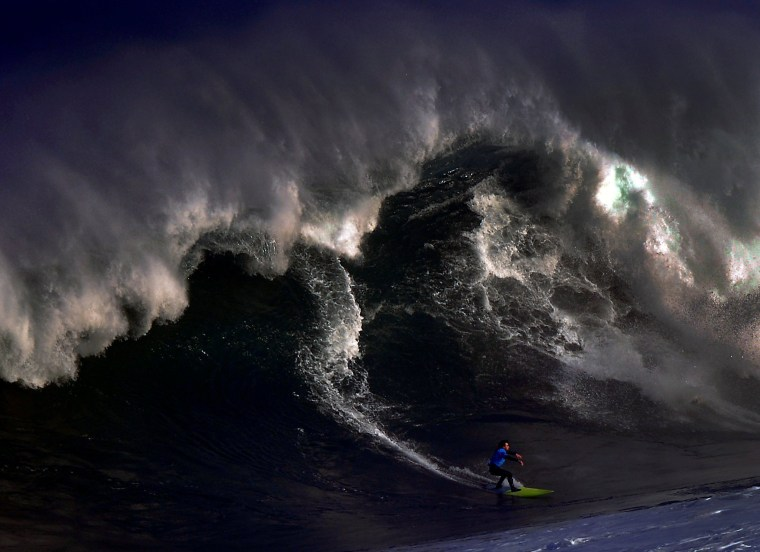 Image: A surfer rides a large wave at El Bocal during the Vaca Gigante giant wave surf competition in Santander