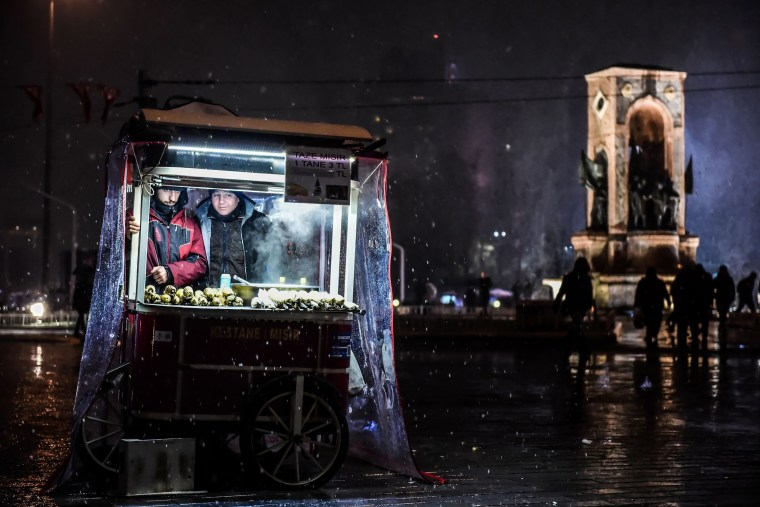 Image: Street vendors sell chestnuts under the snow at Taksim Square in Istanbul on Dec. 16.