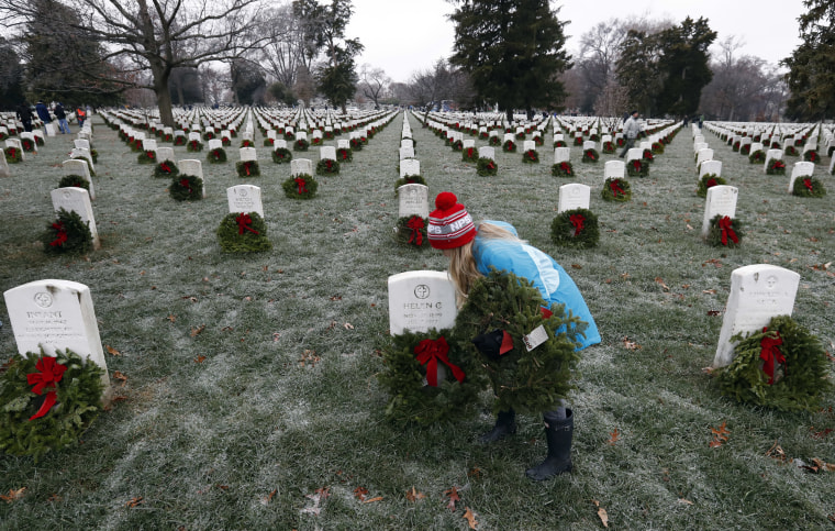 Image: Madeline Espinosa, 11, of Bethesda, Md., places a wreath at a grave as part of Wreaths Across America at Arlington National Cemetery, Dec. 17, in Arlington, Virginia.