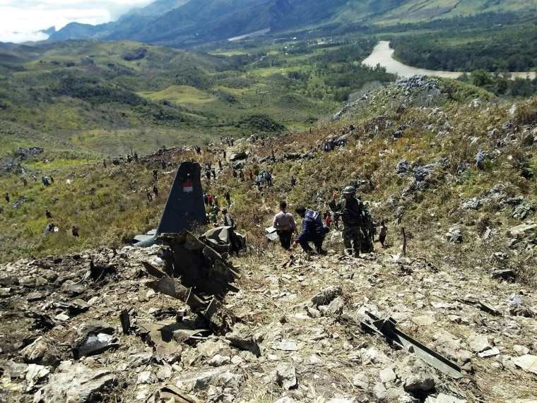Image: Rescue teams and locals are seen at the crash site of Indonesian air force transport plane which killed all 13 people board, on Mount Lisuwa, near Wamena in the remote region of Papua, Indonesia