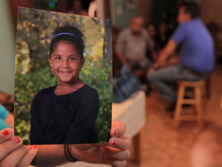 "In this file photo from December 14, 2012, in Maunabo, Puerto Rico, a relative at the house of Elba Marquez, grandmother of 6-year-old Ana Marquez-Greene, holds a photo of the little girl who was killed in the Newtown school shooting. Her father, renowned jazz musician Jimmy Greene, is producing an album in Ana's honor called ""Beautiful Life."""