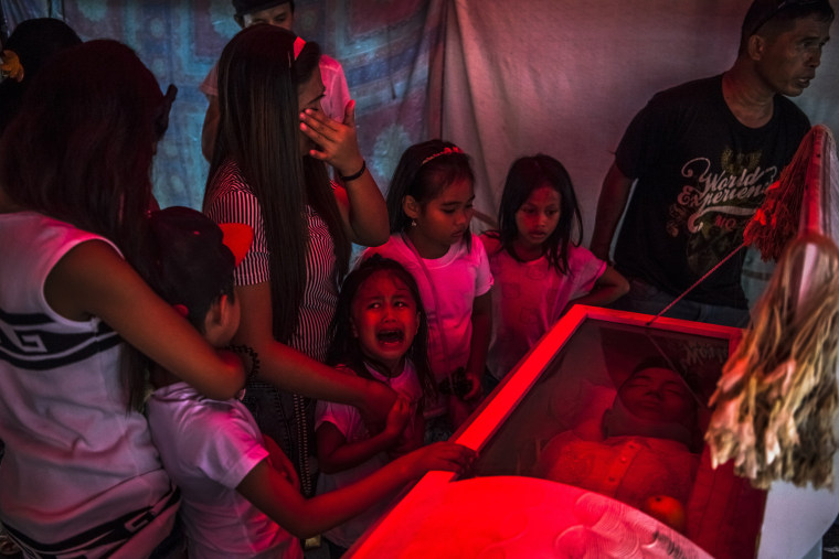 "Image: Jimji, 6, cries out in anguish, saying ""Papa"" as workers move the body of her father, Jimboy Bolasa, 25, for burial, in Manila, Philippines."