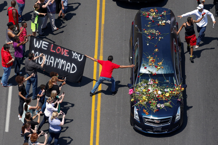 Image: Well wishers holding a banner touch the hearse carrying the body of Muhammad Ali in Louisville Kentucky