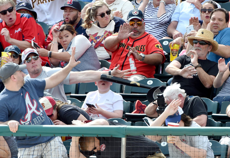 Image: A fan knocks down a bat thrown into the stands by the Pirates' Danny Ortiz