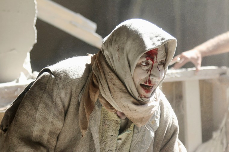 Image: An injured woman reacts at a site hit by airstrikes in the rebel held area of Old Aleppo