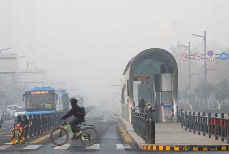 Image: A cyclist crosses a smog-shrouded street