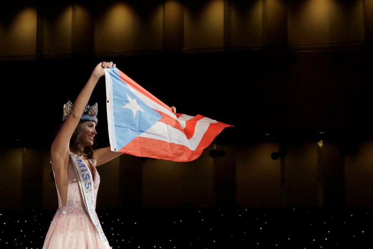 Miss Puerto Rico Stephanie Del Valle holds up the Puerto Rican flag after winning the Miss World 2016 Competition in Oxen Hill, Maryland.