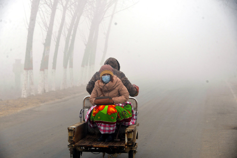 Image: A woman sits on the back of a motorcycle in smog during a polluted day in Liaocheng