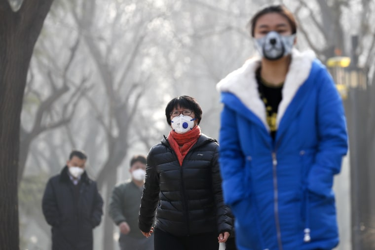 Image: Chinese people wearing masks for protection against pollution walk at Ritan Park