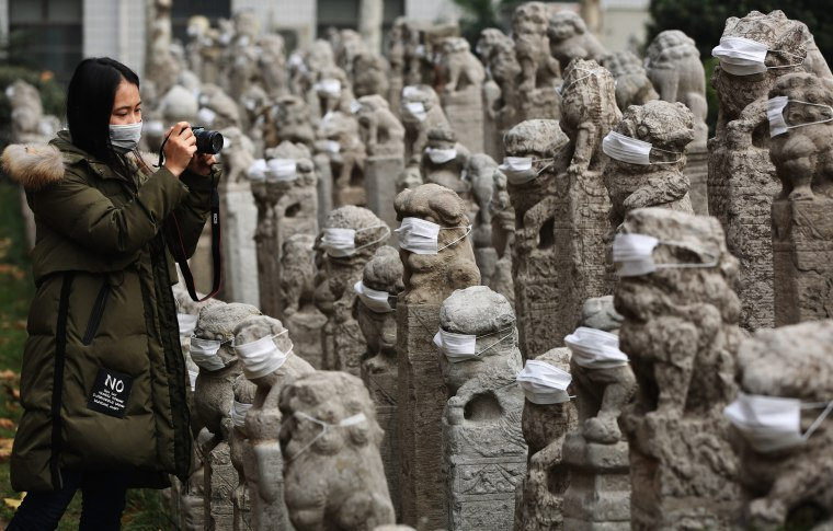 Image: Chinese students put mask on stone lions to raise awareness of air pollution