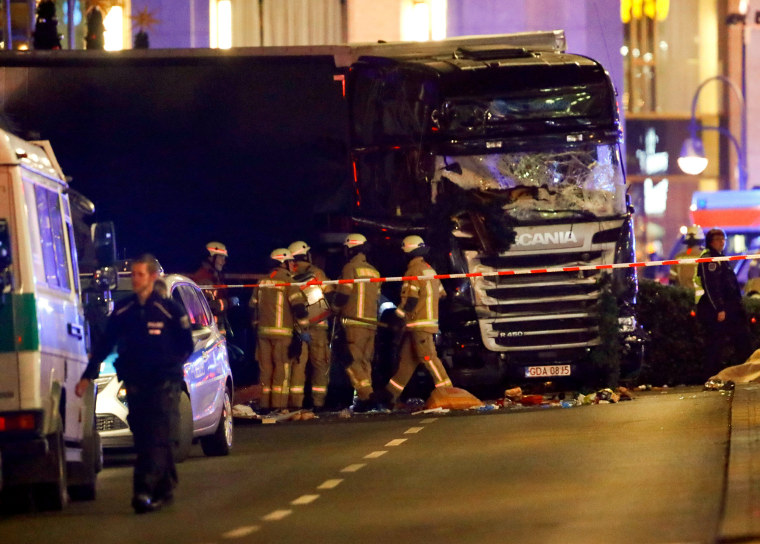 Image: Police and emergency workers stand next to a crashed truck at a Christmas market in Berlin