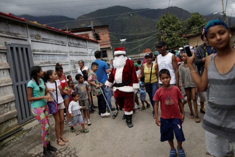 Image: Santa Claus walks during a visit to residents of the slum of Petare in Caracas