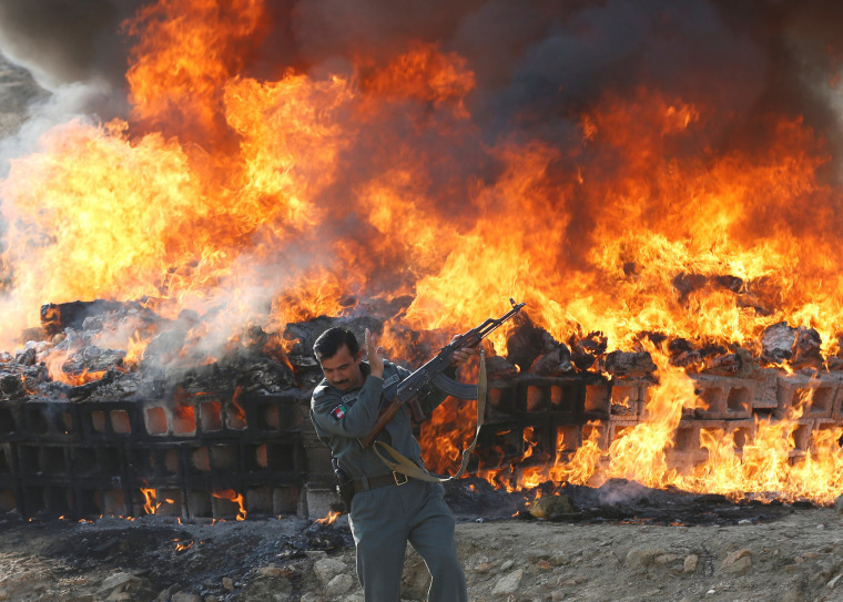 Image: An Afghan officer reacts in front of a burning pile of seized narcotics and alcoholic drinks, in the outskirts of Kabul