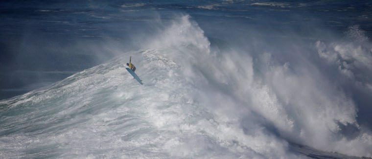 Image: South African surfer Grant Baker drops in on a large wave during the Nazare Challenge championship at Praia do Norte in Nazare