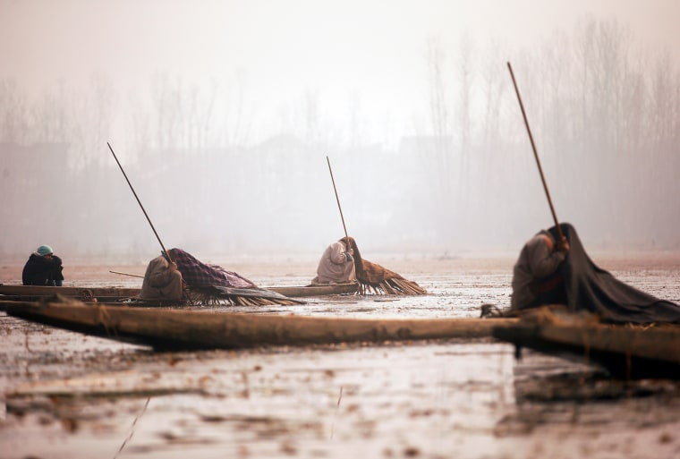 Image: Kashmiri fishermen cover their heads and part of their boats with blankets and straw as they wait to catch fish in the waters of the Anchar Lake on a cold day in Srinagar