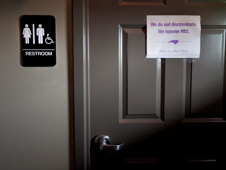 """Image: A unisex sign and the """"We Are Not This"""" slogan are outside a bathroom at Bull McCabes Irish Pub on May 10, 2016 in Durham, N.C."""