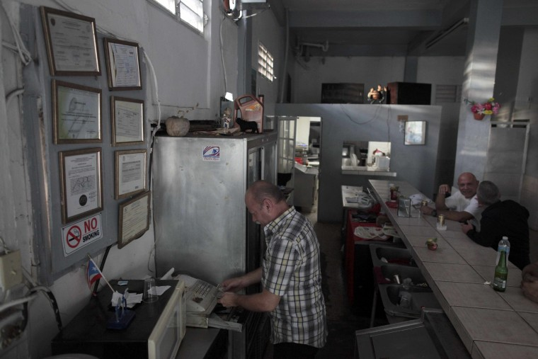 Image: Roberto Torres, checks the cash register next to government-issued licences and permits at his bar in San Juan