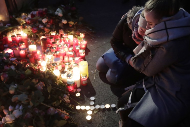Image: Two women mourn beside candles in Berlin, Germany, Dec. 20, 2016, the day after a truck ran into a crowded Christmas market nearby and killed several people.