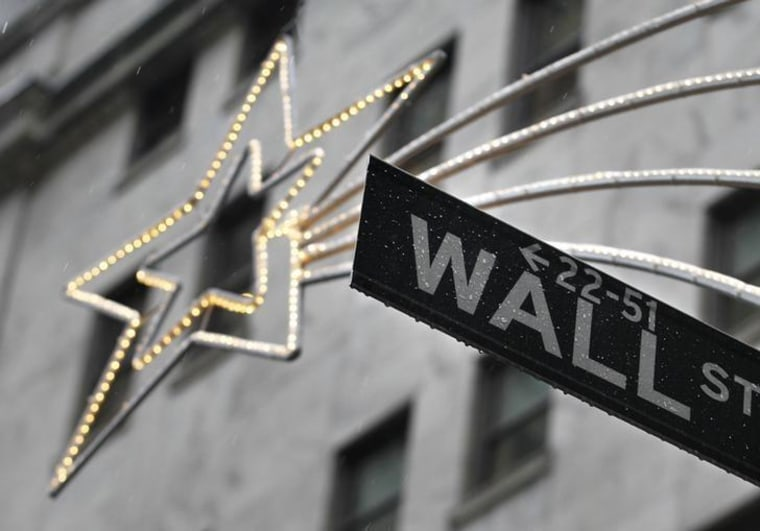 A holiday decoration is seen over Wall St. sign outside the New York Stock Exchange
