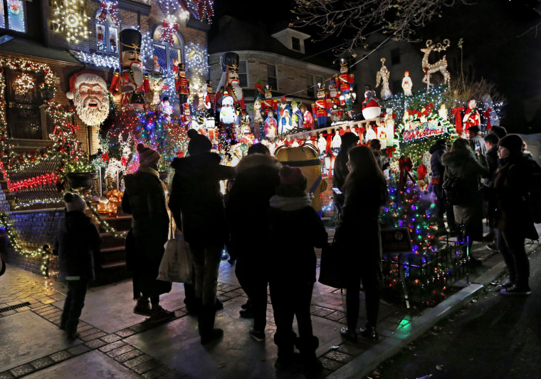 Image:In this Dec. 14, 2016 photo, visitors to the Dyker Heights neighborhood of the Brooklyn Borough of New York gather in front of Lucy Spata's house, as they tour the area known for it's elaborate and over-the-top Christmas displays.