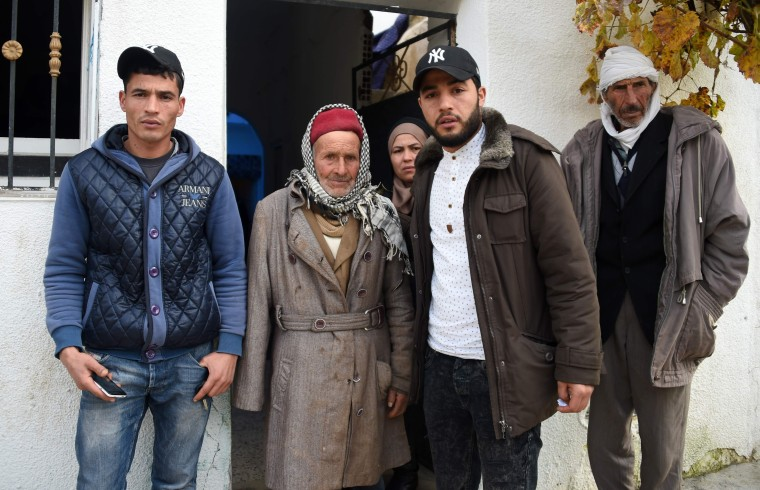 Image: Terror suspect Anis Amri's father Mustapha (second left), brother Walid (L), Hanan (C), and in front the family house in Oueslatia, Tunisia.