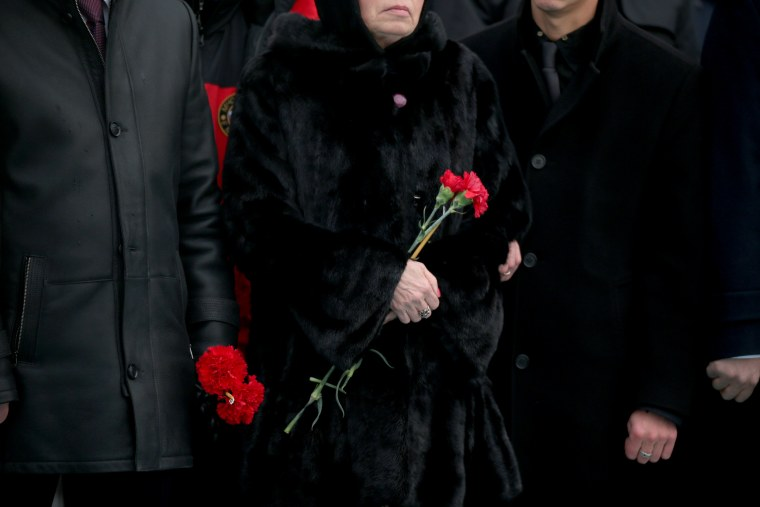 Image: Marina, the wife of Russian Ambassador to Turkey Andrei Karlov who was assassinated Monday, holds flowers during a ceremony at the airport in Ankara, Turkey, Dec, 20.