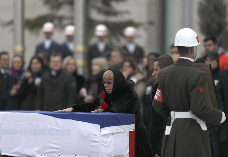 Image: Late Russian Ambassador to Turkey Andrei Karlov's wife Marina reacts next to the flag-wrapped coffin during a ceremony at Esenboga airport in Ankara, Turkey, Dec. 20.