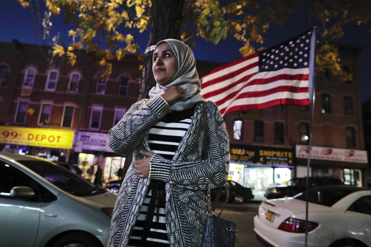 Image: Enas Almadhwahi, an immigration outreach organizer for the Arab American Association of New York, stands for a photo along Fifth Avenue in the Bay Ridge neighborhood of Brooklyn, Nov. 11, 2016.