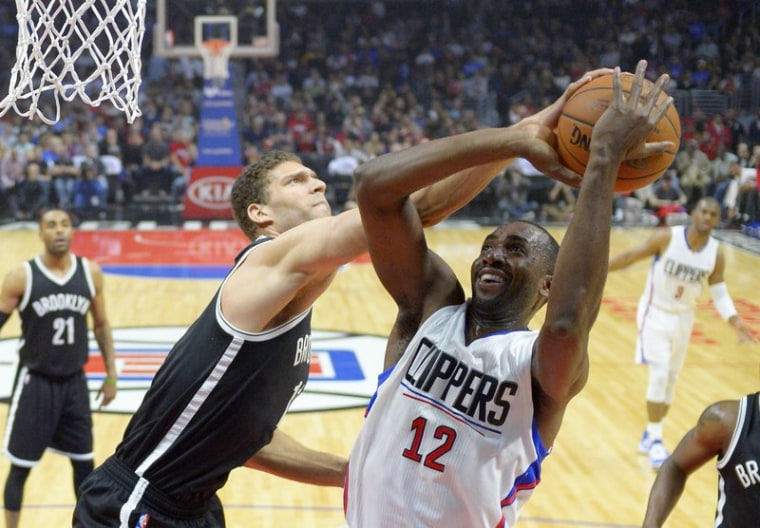Los Angeles Clippers forward Luc Mbah a Moute (R), of Cameroon, shots as Brooklyn Nets center Brooke Lopez defends in Feb. 29, 2016 game.