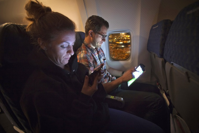 Image: People use their smart devices on an American Airlines airplane, which is equipped with Gogo Inflight Internet service, enroute from Miami to New York.