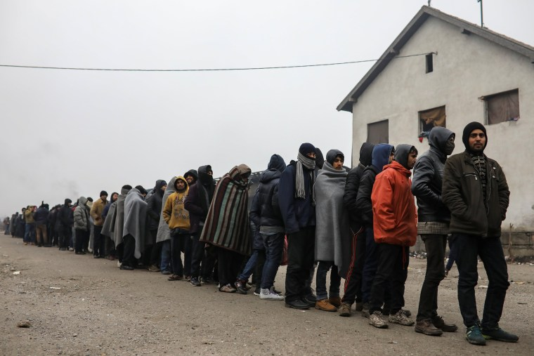 Image: Migrants stand in line to receive free food outside a derelict customs warehouse in Belgrade