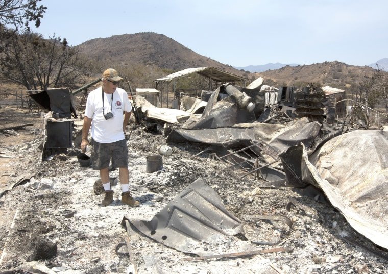Steve Keeling walks through the ashes of his fire ravaged home, Monday, June 27, 2016, in South Lake, Calif. The home was one of the homes and structures that were destroyed by the fire that started Thursday, near Lake Isabella, Calif.