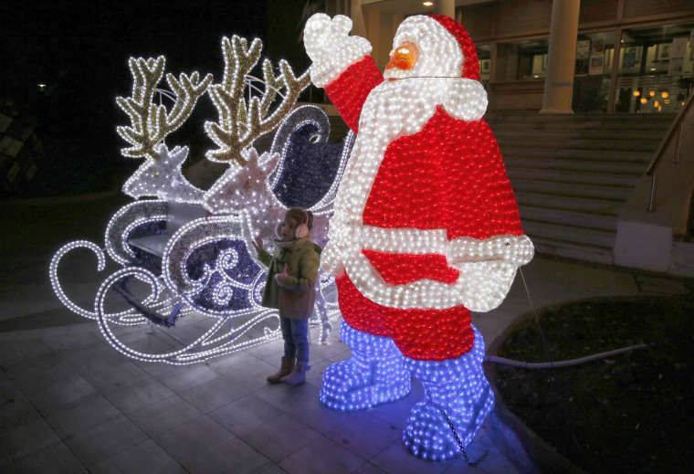 Image: A child poses for pictures in front of Christmas decorations in Mytilene, in the northeastern island of Lesbos, Greece, Dec. 15.