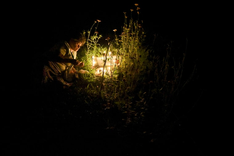 """Image: A woman lights Christmas candles before the grave of a relative at the \""""Jardines de la Aurora\"""" cemetery in Cali, department of Valle del Cauca, Colombia, on Dec. 7, 2016."""
