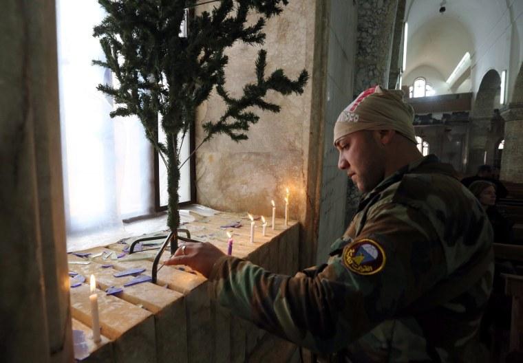 Image: An Iraqi soldier lights candles during Christmas celebrations at the al-Tahira al-Kubra church