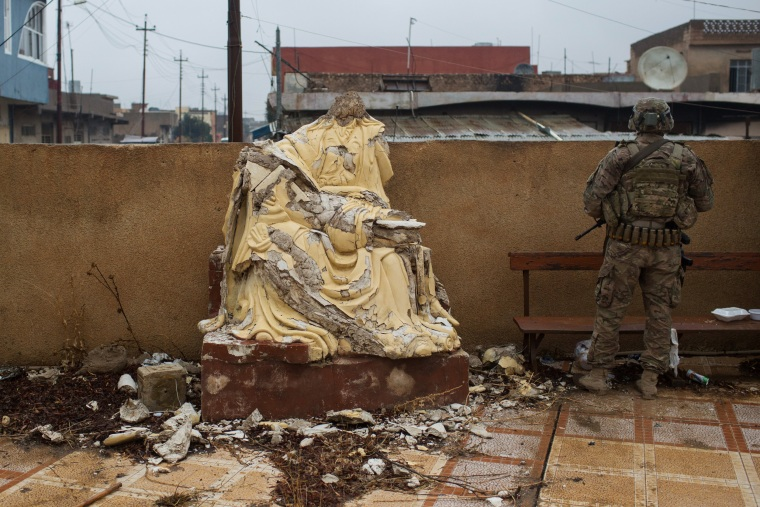 Image: A soldier from the U.S Army stands guard next to a defaced christian statue during Christmas Day mass at Mar Hanna church in Qaraqosh