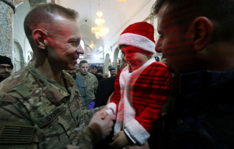 Image: A U.S. Soldier shakes hands with an Iraqi boy during a Christmas Eve service