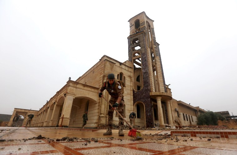 Image: Iraqi security forces clean the square of Saint John's Church before a Christmas Eve service