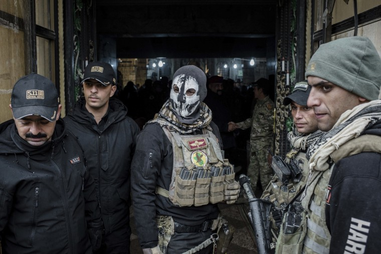 Image: Iraqi forces guard the entrance to a Christmas Eve's Mass at the Assyrian Orthodox church of Mart Shmoni