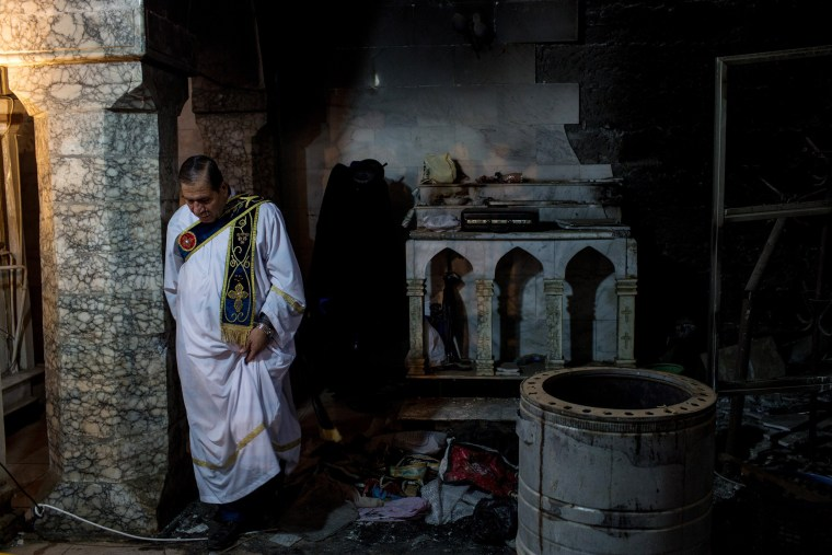 Image: A Deacon walks amongst rubble in a destroyed part of the church after taking part in the Christmas mass