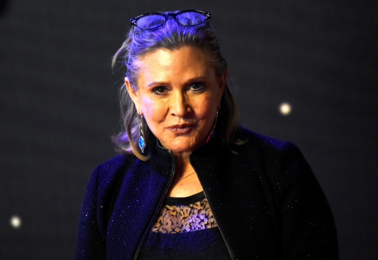 Image: Carrie Fisher poses for cameras as she arrives at the European Premiere of Star Wars, The Force Awakens in Leicester Square, London