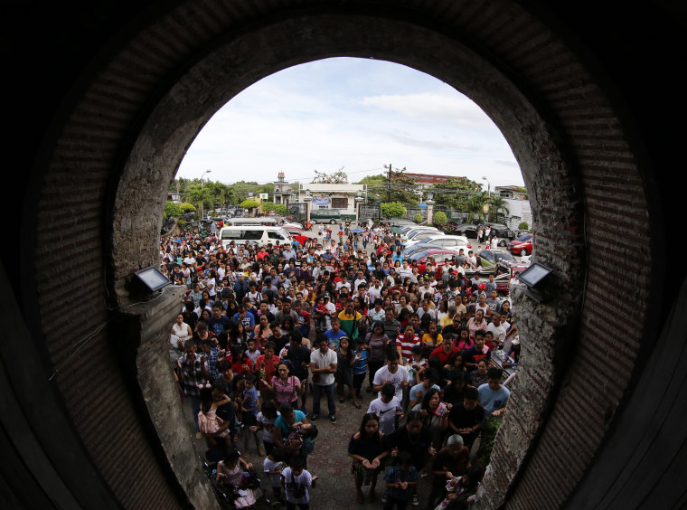Image: Filipino villagers hear mass in front of a church on Christmas Day