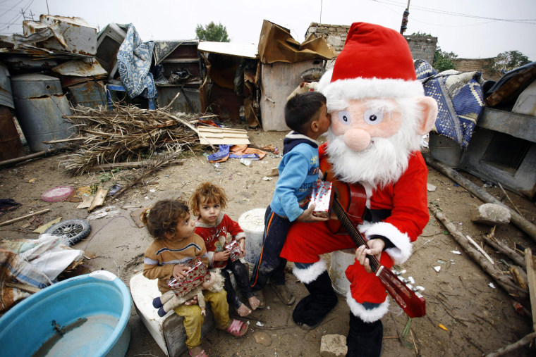 Image: An Iraqi odontology student dressed as Santa Claus distributes gifts to impoverished children