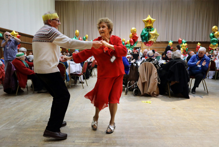 Image: Anita Monk and her neighbor John Everett dance during a Christmas dinner