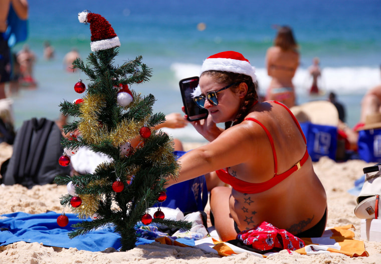 Image: Irish backpacker Genna Woods adjusts her small Christmas tree she planted in the sand as she celebrates Christmas Day at Sydney's Bondi Beach in Australia