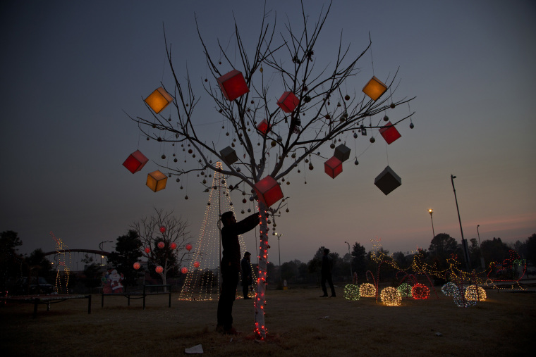 Image: A Pakistani man decorates a tree in a Christian neighborhood of Rawalpindi
